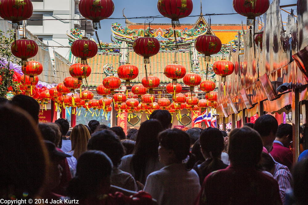 31 JANUARY 2014 - BANGKOK, THAILAND:   People walk into Wat Mangkon Kamalawat beneath Chinese lanterns during Lunar New Year festivities, also know as Tet and Chinese New Year, in Bangkok. This year is the Year of the Horse. Ethnic Chinese make up about 14% of Thailand and Chinese holidays are widely celebrated in Thailand.     PHOTO BY JACK KURTZ