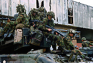 US soldiers ride on a tank and position themselves to secure a neighborhood from Panamanian army troops during the US invasion of Panama, December 1989.