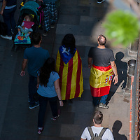 "Tuesday, 03 October 2017. Barcelona, Catalonia.  Catalan referendum. People gathered in Barcelona. A couple walks on Carrer Carders street in Barcelona old quarter carring a Estelada (Catalan independentist flag) and a Spanish flag with ""Not to violence"" writed on it. The spanish State is promoting the idea of a violent fracture in the Catalan society. As a reaction for the brutality of the spanish police and to support the results of referendum a general strike was decalred on Tuesday 3rd of October 2017."