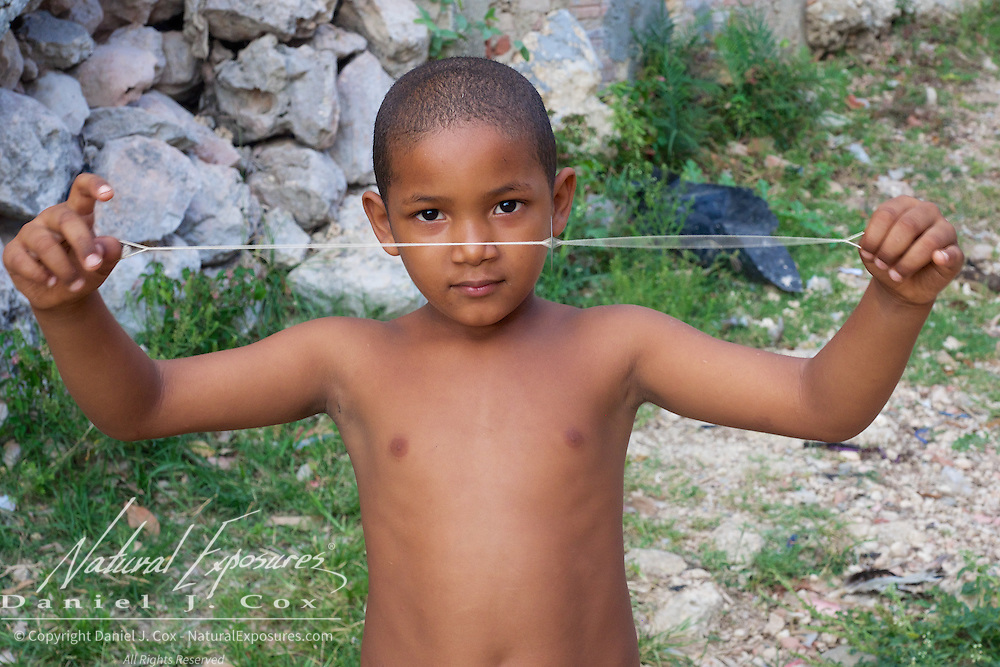 A young boy having fun with a simple washer on a string, Trinidad, Cuba.