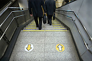 businessmen walking down stairs with direction arrows train station Japan Tokyo