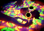 Young man with glowing goggles lying in a pile of glowing packing peanuts.Black light