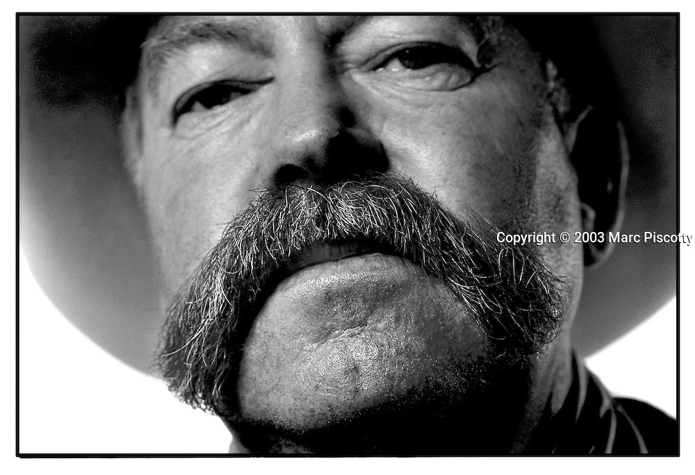 "SHOT 1/17/2003 - Cattle buyer John L. Regier of Lethbridge, Alberta shows off his moustache during the National Western Stock Show and Rodeo recently. Regier owns Grass Roots Consulting and consults on the breeding and raising of stock and feeder cattle. He said it was his fifth time at the National Western and was there making contacts and checking up on the state of the industry. The National Western Stock Show is held every January at the National Western Complex in Denver, Colorado. First held in 1906, it is the world's largest stock show by number of animals and offers the world?s only carload and pen cattle show in the historic Denver Union Stockyards. The stock show is governed by the Western Stock Show Association, a Colorado 501 (c) 3 institution, which produces the annual National Western Stock Show in an effort to forward the association's mission: ""To preserve the western lifestyle by providing a showcase for the agricultural industry through emphasis on education, genetic development, innovative technology and offering the world's largest agricultural marketing opportunities."" Proceeds from the National Western Stock Show go to the National Western Scholarship Trust. The Trust awards 64 scholarships annually to students studying agriculture and medicine to practice in rural areas at colleges and universities in Colorado and Wyoming..(Photo by Marc Piscotty / © 2003)"