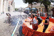 Picture by Andrew Tobin/Tobinators Ltd +44 7710 761829<br /> 04/08/2013<br /> Bathers splash a competitor to cool them down during the Cycle Messenger World Championships held in Lausanne, Switzerland. Started in 1993 by Achim Beier from Berlin, the championships are not only a sporting contest but an opportunity to unite friends and bicycle enthusiasts worldwide. The event comprises a number of challenges including a sprint, a track stand (longest time stationary on the bike), a cargo race where heavy loads are carried on special bikes, and the main race. The course winds through central Lausanne and includes bridges, stairs, cobbles, narrow alleyways and challenging hills. The main race simulates the job of a bike courier making numerous drops and pickups across the city. Riders need to check in at specific checkpoints, hand over their delivery and get a new one. The main race can take up to 4 hours for each competitor to complete.