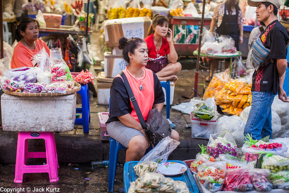 19 OCTOBER 2012 - BANGKOK, THAILAND:   Vendors in the Bangkok Flower Market. The Bangkok Flower Market (Pak Klong Talad) is the biggest wholesale and retail fresh flower market in Bangkok.  The market is busiest between 3:30AM and 6AM. Thais grow and use a lot of flowers. Some, like marigolds and lotus, are used for religious purposes. Others are purely ornamental.        PHOTO BY JACK KURTZ