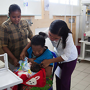 Flaviana breast feeding her new born baby, Maria, helped by Alola health worker Beatrize. Flaviana gave birth to Maria the day before but because Maria had fever she was kept in the ante-natal ward while Flaviana was recovering from cesarian. This is their first attempt to connect and for Maria to breast feed and with the help of Beatrize they succeed.  Infant mortality rates are very high in Timor-Leste and one of the reasons for that is poor nutrition. Alola advocate breast feeding till at least two years old and teach women about nutritious supplements such as boiled and mashed rice w vegetables and eggs.  Fundasaun Alola is a not for profit non government organization operating in Timor Leste to improve the lives of women and children. Founded in 2001 by the then First Lady, Ms Kirsty Sword Gusmao, the organization seeks to nurture women leaders and advocate for the rights of women.