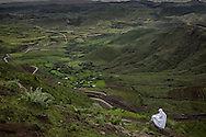 Woman descends the mountain to her village after worshipping in a church further up in the Ethiopian Highlands.