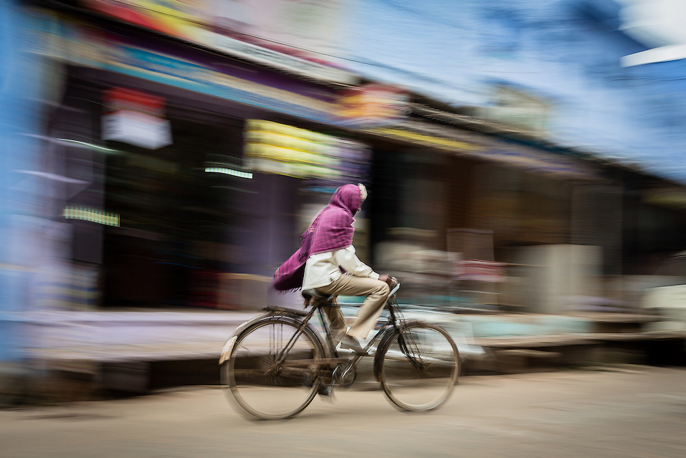 A panning shot of a man riding his bycicle through one of the main streets of Bundi