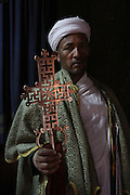 An Orthodox Christian priest holds a golden cross from one of the rock-hewn churches in Lalibela. Declared a UNESCO World Heritage Site, Lalibela's rock-hewn churches were built in the 12th and 13th centuries and are said to represent a miniature version of Jerusalem. Located at 2,500 meters above sea level, Lalibela is one of Ethiopia's holiest cities and a center of pilgrimage for the Ethiopian Orthodox Christian population. Lalibela, Amhara Division, Ethiopia. March 31, 2011.