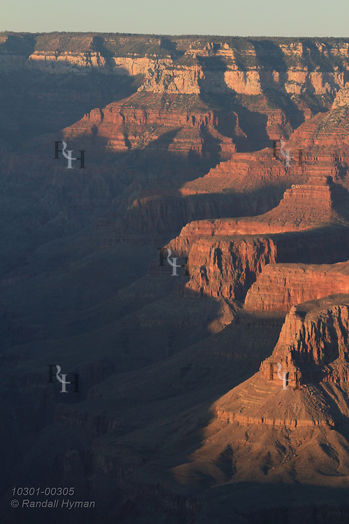 Buttes and red cliffs dominate landscape in sunset view of Bright Angel Trail region; Grand Canyon Village, South Rim, Grand Canyon National Park, Arizona.