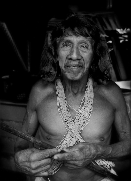 """""""Afectado"""" (Affected One): Davo Enemenga, a Huaorani man whose ancestral land has been contaminated by oil exploration by Chinese government-owned, Petro Oriental.  """"They promised to help us (the local Huaorani residents) and did not"""", says Enomenga.  """"They caused us problems.  They paid us nothing, no cash (his word, """"silver"""" coins or cash).  They cheated us"""".  Proveta, south of Coca, Ecuador.<br /> <br /> According to the company website, """"PetroOriental S.A. are companies established through capital provided by state-run firms from the People's Republic of China.  These include: China National Petroleum Corporation (CNPC) with 55% shareholder participation and China Petrochemical Corporation (SINOPEC) with 45% shareholder participation."""""""