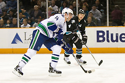 April 8, 2010; San Jose, CA, USA; Vancouver Canucks left wing Alex Burrows (14) is defended by San Jose Sharks defenseman Rob Blake (4) during the first period at HP Pavilion. San Jose defeated Vancouver 4-2. Mandatory Credit: Jason O. Watson / US PRESSWIRE