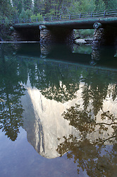 El Capitain reflects into the Merced river near a bridge in Yosemite National Park, California.