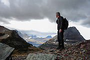 New York Times correspondent, Michael Wines, standing atop a lateral moraine of a former glacier at the base of Mount Clements at Logan Pass, Glacier National Park, Montana, Tuesday, October 7, 2014. Sperry Glacier at the top of Gunsight Mountain is visible in the distance.
