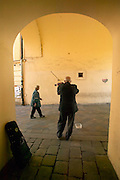 Europe, Slovakia, capitol city - Bratislava.street musician plays his violin in the arches on the Micheal tower midieval city gate.