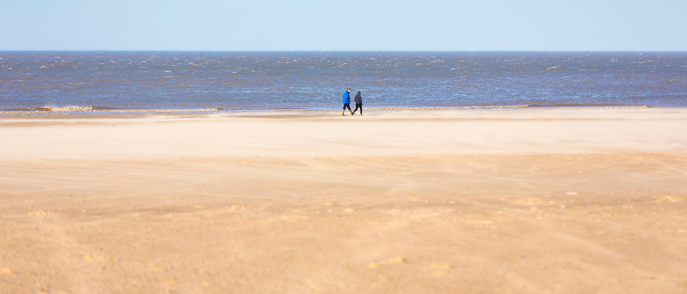 People walking along Holkham Beach, a vast sandy beach on North Norfolk coast, UK