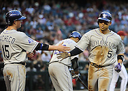 PHOENIX, AZ - APRIL 26:  Carlos Gonzalez #5 of the Colorado Rockies is congratulated at home plate by teammate Jordan Pacheco #15 after scoring on an RBI double hit by Michael Cuddyer (not pictured) against the Arizona Diamondbacks in the first inning at Chase Field on April 26, 2013 in Phoenix, Arizona. (Photo by Jennifer Stewart/Getty Images)
