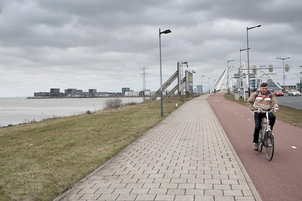 Een fietser rijdt over de brug bij het Steigereiland, onderdeel van de nieuwbouwwijk IJburg bij Amsterdam.<br /> <br /> A cyclist is passing a bridge near Steigereiland, part of the new neighborhood IJburg in Amsterdam.