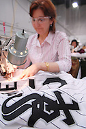 4/3/09 10:47:18 AM -- Easton, PA, U.S.A. -- Djoumile Pendeva, a seamstress at Majestic Athletic sews lettering on the back of a Chicago White Sox jersey April 3, 2009 in Easton, Pennsylvania. White Sox jerseys and gear have experienced a boost in sales with Obama, a White Sox fan, in the White House. -- .Photo by William Thomas Cain,  cainimages.com.
