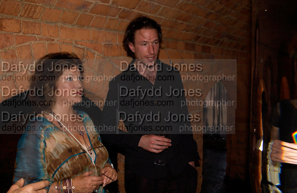 Lady Ashcombe and Petroc Sestie xplaining his work called 'Event Horizon' in the Sudeley Castle Dungeons.  . Mollie Dent-Brocklehurst and Vanity Fair host  the opening of 'Vertigo'  a mixed art exhibition at Sudeley Castle. Winchombe, Gloucestershire. 18 June 2005. ONE TIME USE ONLY - DO NOT ARCHIVE  © Copyright Photograph by Dafydd Jones 66 Stockwell Park Rd. London SW9 0DA Tel 020 7733 0108 www.dafjones.com