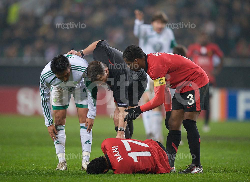 Fussball Uefa Champions League VFL Wolfsburg - Manchester United FC V.l.: Makoto HASEBE (Wolfsburg), Schiedsrichter Bjorn KUIPERS (NED) und Patrice EVRA (Manchester) interessieren sich fuer die Gesundheit von NANI (Manchester).