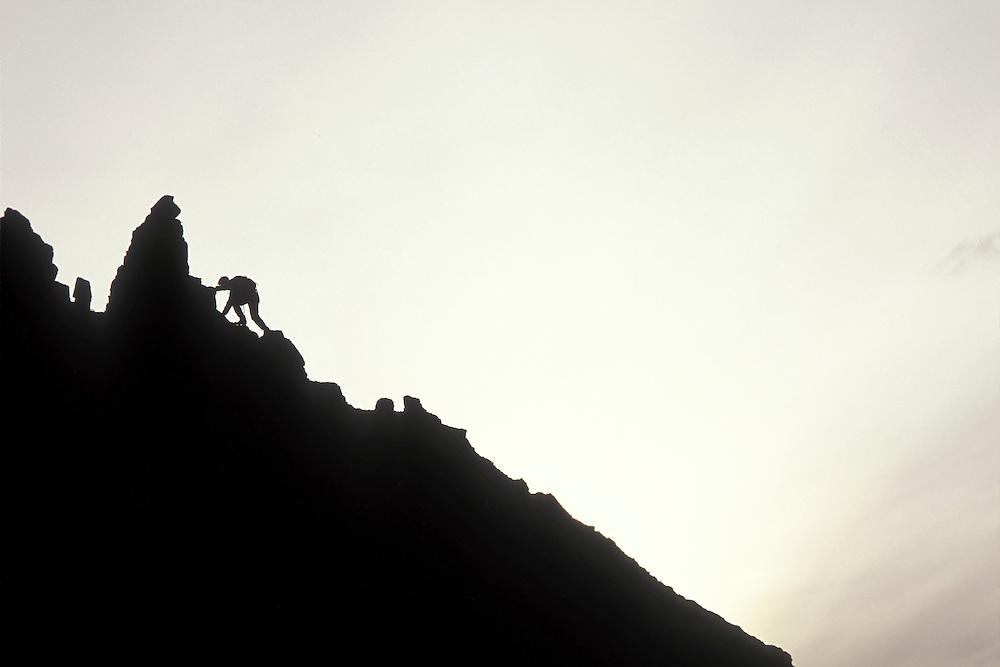 USA, Alaska, Chugach State Park, (MR) Alyson Pytte climbs jagged ridge near Twin Peaks in Chugach Mountains