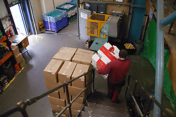 Man with learning disability carrying flat packed cardboard down factory stairs in preparation for assembling cardboard boxes,