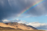 A rainbow forms as a rainstorm blows through the dry hills near the Columbia River gorge.