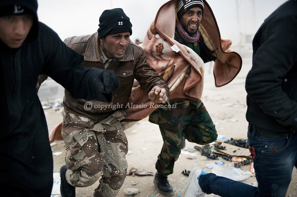 "LIBYA, BREGA : Anti Libyan government fighters rush for cover as heavy shelling by forces loyal to Libyan strongman Moamer Kadhafi fall close to their position in the eastern town of Brega on March 13, 2011. Libyan state television said the town had been ""purged"" of insurgents. ALESSIO ROMENZI"