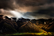 Stormclouds gather around Afton Peak and farm buildings, Lake Wakatipu, New Zealand.