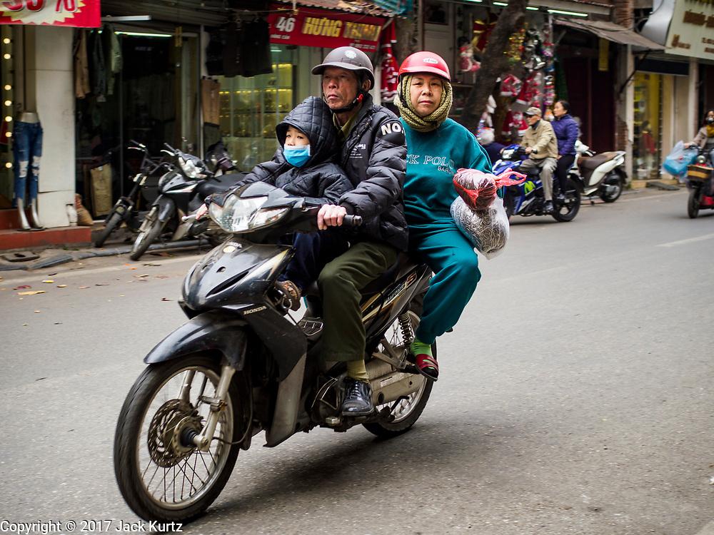 24 DECEMBER 2017 - HANOI, VIETNAM: A family on a motorscooter in the old quarter of Hanoi.       PHOTO BY JACK KURTZ