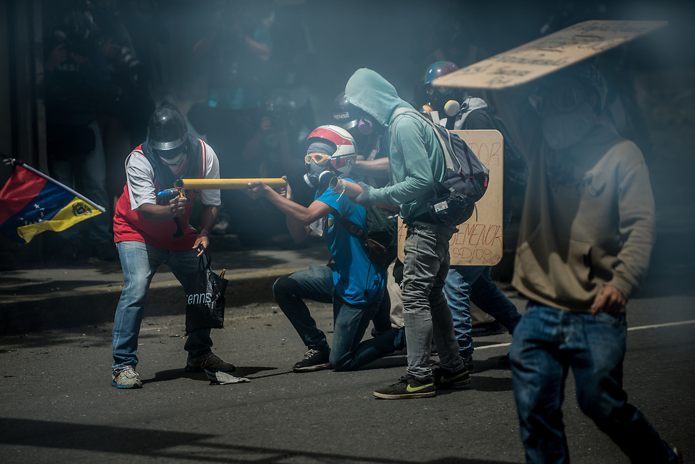 CARACAS, VENEZUELA - MAY 24, 2017:  Anti-government protesters launch fire crackers at members of the National Police during clashes.  Authorities responded by heavily tear gassing and firing rubber bullets and buckshot at them. The streets of Caracas and other cities across Venezuela have been filled with tens of thousands of demonstrators for nearly 100 days of massive protests, held since April 1st. Protesters are enraged at the government for becoming an increasingly repressive, authoritarian regime that has delayed elections, used armed government loyalist to threaten dissidents, called for the Constitution to be re-written to favor them, jailed and tortured protesters and members of the political opposition, and whose corruption and failed economic policy has caused the current economic crisis that has led to widespread food and medicine shortages across the country.  Independent local media report nearly 100 people have been killed during protests and protest-related riots and looting.  The government currently only officially reports 75 deaths.  Over 2,000 people have been injured, and over 3,000 protesters have been detained by authorities.  PHOTO: Meridith Kohut
