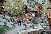 An old man carrying a sack of peas through the village of Chitkul, Kinnaur