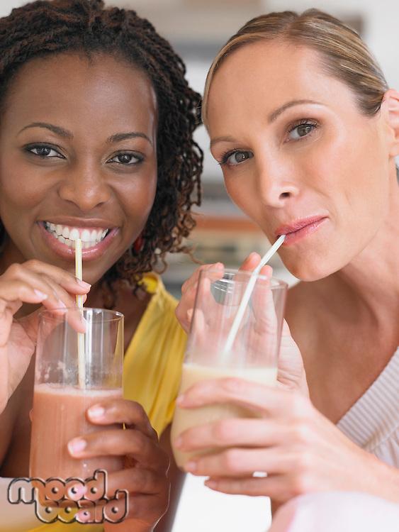Two women drinking milkshake portrait