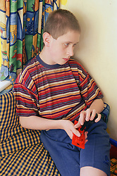 Teenage boy with autism holding plastic toy,