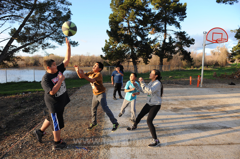 Kids play basketball in the setting sun after a community cleanup on Tuesday, February 2nd, 2016 at the nearly-completed Acosta Plaza Recreation Area in east Salinas, CA.