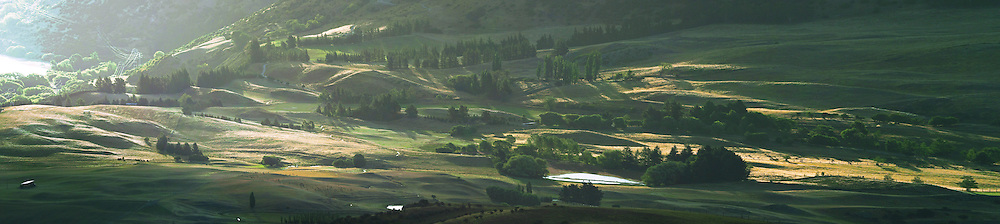 Farmlands illuminated by the setting sun, Central Otago, New Zealand.