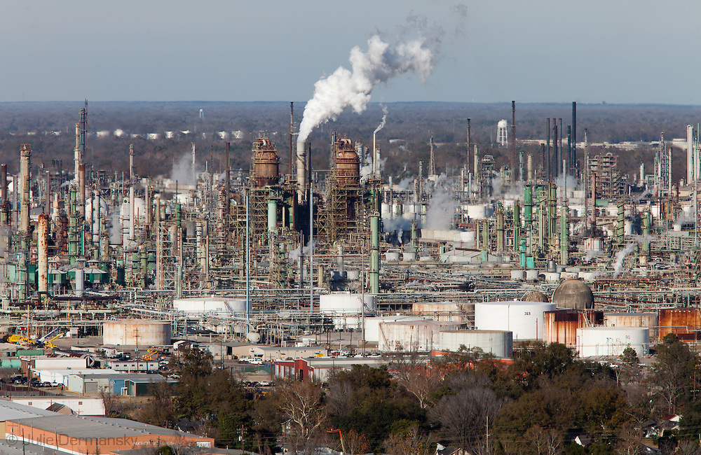 """View from the Louisiana State Capital building in Baton Rouge of the Exxon Mobile refinery located  across from  the Mississippi River in the stretch between Baton Rouge and New Orleans,  is part of a large concentration of chemical and oil companies that was formerly referred to as the """"Petrochemical Corridor,"""" but now is know as """"Cancer Alley.""""  Many cases of cancer have occurred  in communities on both sides of the river though the Louisiana Tumor Registry claims the numbers are not higher then the national average. The record high levels of the Mississippi River in the spring of 2011 brought on by what some scientists classify as climate change,  threaten the environment with the potential flooding of industrial complexes and nuclear facilities along the river."""