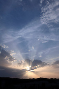 rays of sunlight with clouds and rural hilly landscape