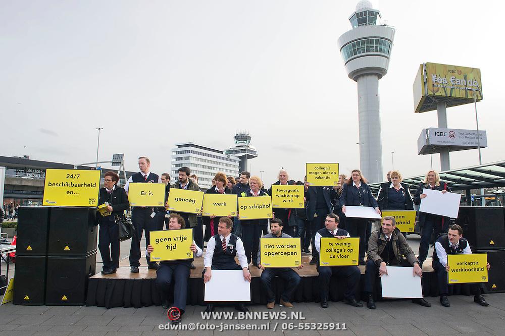 Schiphol, 06-02-2014. Afroepers(oproepkrachten) in dienst van het beveiligingsbedrijf G4S Aviation Service op Schiphol voeren actie voor meer zekerheid. Afroepers werken op de luchthaven letterlijk op afroep: ze moeten 24/7 beschikbaar zijn om te komen werken. Maar ze krijgen steeds minder uren werk aangeboden. Dat betekent voor velen financiele problemen en geen priveleven. Dat ze minder werk krijgen aangeboden is vreemd, want Schiphol groeit en ook G4S neemt constant nieuwe mensen aan. De actie was georganiseerd door FNV Beveiliging.