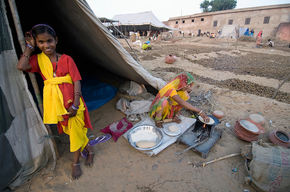 Smiling girl in the doorway of her tent while her mother prepares chapatis (unleavened bread) for dinner.