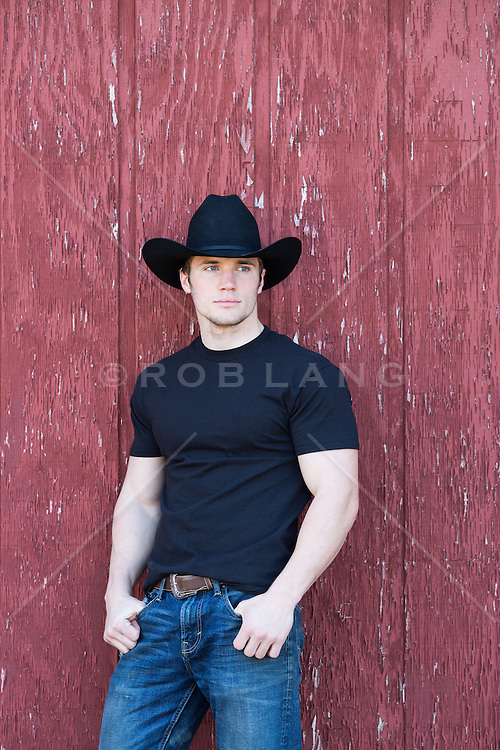 portrait of a hot cowboy in a black tee shirt leaning against a rustic barn