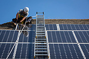 A maintenance person uses a ladder and harnesses to install equipment around a Solar panel array on the roof of a house to stop birds nesting underneath. Folkestone, Kent, United Kingdom.  (photo by Andrew Aitchison / In pictures via Getty Images)