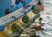 "Yellow boat bumpers reflect in rippled water of the Pacific Ocean. Puerto Ayora is capitol of Santa Cruz Island, and the largest town in the Galápagos Islands archipelago, a province of Ecuador, South America. In 1959, Ecuador declared 97% of the land area of the Galápagos Islands to be Galápagos National Park, which UNESCO registered as a World Heritage Site in 1978. Ecuador created the Galápagos Marine Reserve in 1998, which UNESCO appended in 2001. Published in ""Light Travel: Photography on the Go"" book by Tom Dempsey 2009, 2010."