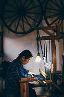 An elderly woman works a cotton loom at the Yamamura indigo workshop in Kyushu, Japan.