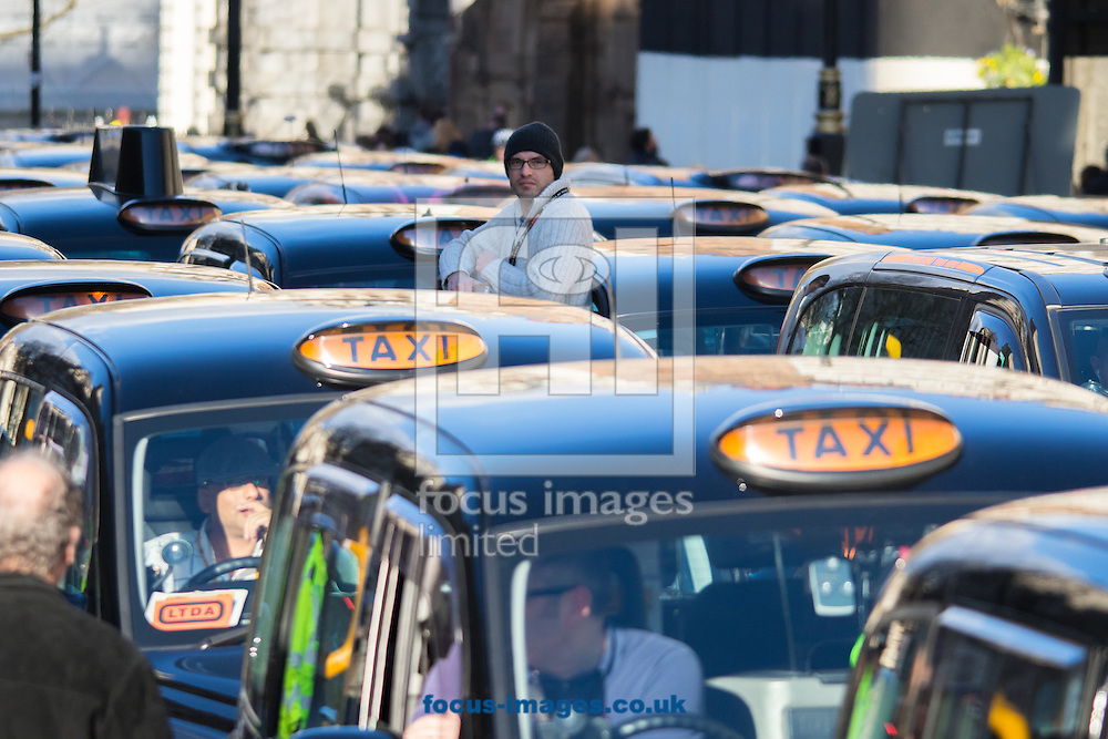 A taxi driverstands amongst his colleagues vehicles as an estimated 8,000 cabbies protest against &quot;unfair competition&quot; from Uber mini cabs<br /> Picture by Paul Davey/Focus Images Ltd +447966 016296<br /> 10/02/2016