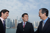 Three business men smiling office buildings in background
