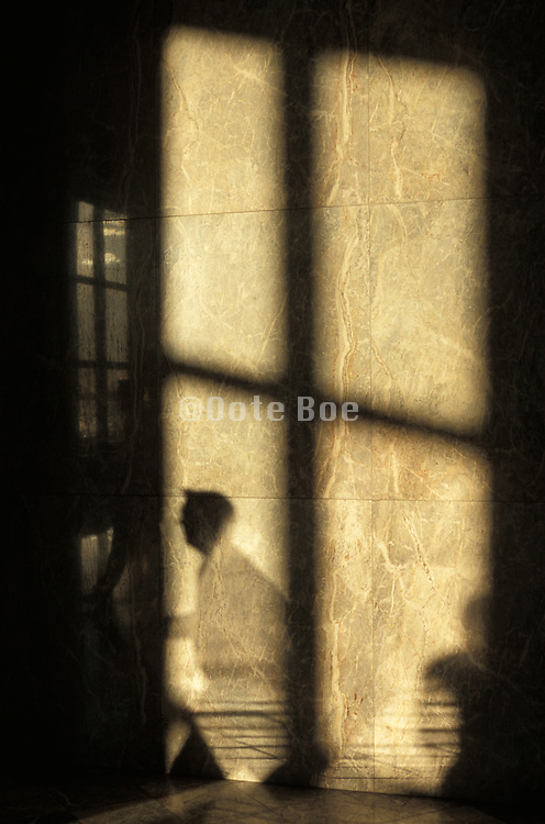 shadow on the wall of a man hurrying