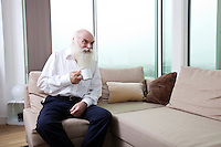 Senior man having coffee while sitting on sofa in apartment