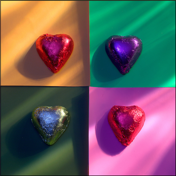 Colorful foil wrapped candy heart confections on a background of colored paper, with dramatic lighting.